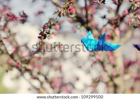 in the spring on verka of a blossoming tree paper cranes hang