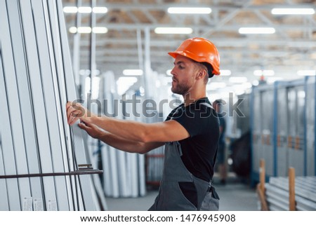 In the storage with many of objects. Industrial worker indoors in factory. Young technician with orange hard hat. #1476945908