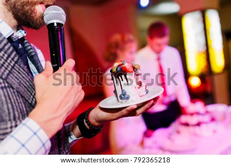 In the style vintage. A wedding cake with Berries decorated with fresh fruits, strawberry, blackberry, blueberry, physalis, chocolate.  The emcee leading in a gray suit demonstrates and hold the cake. Stock photo ©