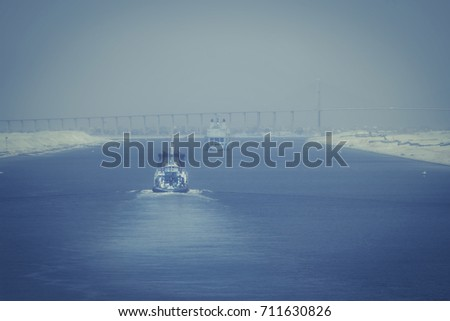 In the Suez Canal - a military ship and a tugboat forward to the city of  El Qantara and the Mubarak Peace Bridge in foggy evening mood #711630826