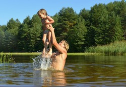 In the summer, bright sunny day, the little girl and man is bathed dives,run, jumps into the river. Beside him spray.