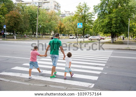 In the summer on the street at the pedestrian crossing father and son and daughter cross the road. Dad holds little hands with his hands.