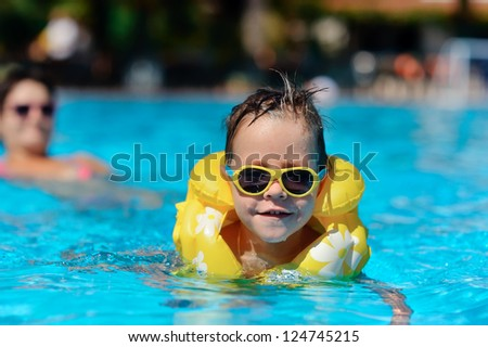 In the sunny day in the summer the boy in sun glasses and in a life jacket floats in pool