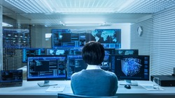 In the System Control Data Center Technician Operates Multiple Screens with Neural Network and Data Mining Activities. Room is Light and Full of Monitors with Working Neural Network on Them.