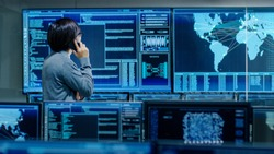 In the System Control Room IT Administrator Talks on the Phone. He's in a High-Tech Facility That Works on the Surveillance, Neural Networks, Data Mining, AI Projects.