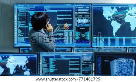 In the System Control Room IT Administrator Talks on the Phone. He's in a High-Tech Facility That Works on the Surveillance, Neural Networks, Data Mining.