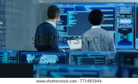 In the System Control Room IT Specialist and Project Engineer Have Discussion, they're surrounded by Multiple Monitors with Graphics. They Work in a Data Center on Data Mining.