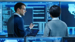 In the System Control Room IT Specialist and Project Engineer Have Discussion while Holding Laptop, they're surrounded by Multiple Monitors with Graphics. They Work in a Data Center on Data Mining.