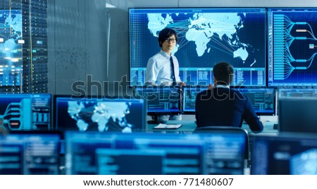 In the System Control Room Manager Holds a Briefing for His Staff Member. They're Work in Data Center and are Surrounded by Multiple Screens Showing Maps, Logistics Data.