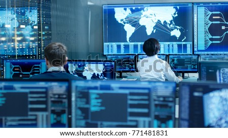 Photo of  In the System Control Room Operator and Administrator Sitting at Their Workstations with Multiple Displays Showing Graphics and Logistics Information.