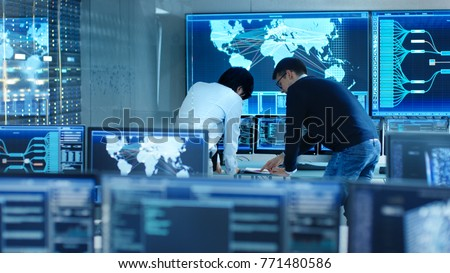 In the System Control Room Project Manage and IT Engineer Have Discussion, they're surrounded by Multiple Monitors with Graphics. Big Monitor Shows Interactive Logistics Map.