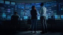 In the System Control Room Project Manager and IT Technical Engineer Have Discussion, they're surrounded by Multiple Monitors with Graphics. Big Monitor Shows Interactive Server Blockchain Info.