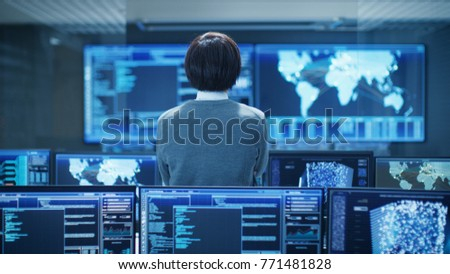 In the System Control Room Technical Operator Stands and Monitors Various Activities Showing on Multiple Displays with Graphics. Artificial Intelligence, Big Data Mining, Neural Network, Surveillance. #771481828