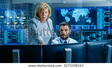 In the System Monitoring Room Senior Supervisor Controls Work of the Operator. They're Surrounded by Monitors Showing Relevant Technical Data. #1073338163