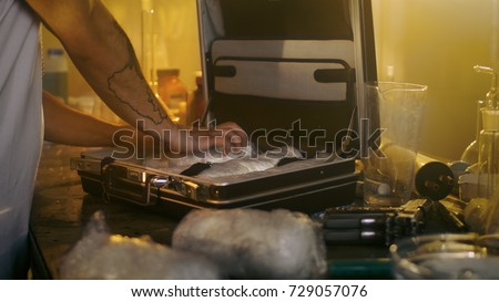Shutterstock In the Underground Laboratory Hardcore Dealer Places Brick Packs Filled with Drugs Into the Suitcase for Further Selling and Distribution. He Squats in the Abandoned Building with Boarded Up Windows.