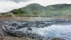 In the valley of hot springs, the mud boiler is filled with a gray liquid. There are bubbles and steam above the surface. Clay edges. Green mountains against a cloudy sky. Kamchatka
