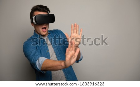 In the virtual game. Close up photo of a stunned man in VR glasses, who is making a defending gesture with his hands.