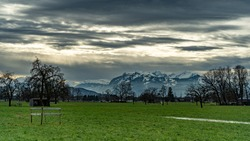 In the Vorarlberg Rhine Valley there are puddles in the fields in which the Swiss mountains are reflected in the background. The Alpstein massif is covered in snow. gloomy evening mood, clouds in sky
