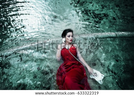 Stock Photo In the water young girl with phone, she in a red dress.