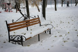 In The Winter Park, An Empty And Lonely Bench Is Completely Covered With Snow. The Snow Is Covered With Leaves That Have Fallen From The Trees.