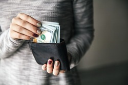 In the women's hands is the brown leather wallet with a wad of hundred dollars. Business offer. Beautiful manicure
