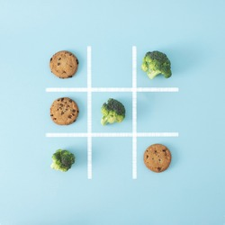 In this board game broccoli beats chocolate chip cookies, that means healthy food is better than junk food, so win this game. Creative flat lay concept.