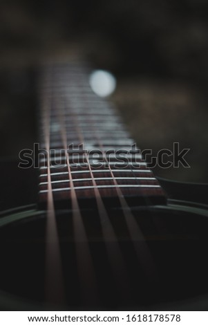 In this image you can see in the frame, the strings of a guitar from a grand opening approach
