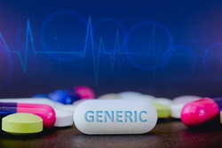 In this photo illustration pills of pharmaceutical drugs of various colors. Text GENERIC in one white pill. Healthcare and medicine concept