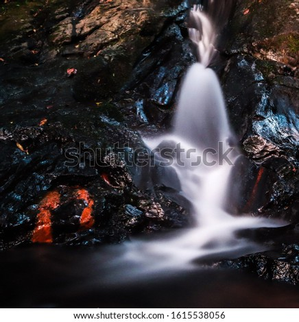 In this photograph you can see a waterfall between rocks, with colored stones and a smooth flow.