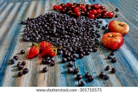 In vintage blue table light falls from a window, lay on the table dark blueberries, fresh strawberries and large juicy peaches