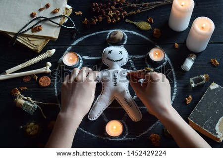 In Voodoo doll are needles pricked. Candles, pentagram, stones, love potion and old books on witch table. Occult, esoteric or divination concept. Mystic, Halloween and vintage background