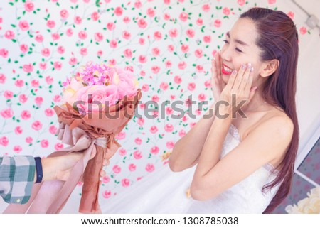 In wedding day. Young Asia bride receive wedding bouquet.She is very glad and surprise.happy, excited, Photo concept marry and ceremony.