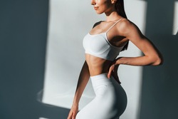 In white sportive clothes. Young caucasian woman with slim body shape is indoors at daytime.