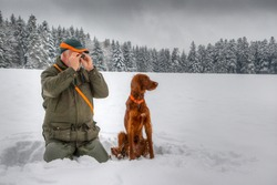 In winter a hunter kneels in the snow and observes his snowy hunting ground through a small eyepiece, next to him sits his beautiful Irish Setter hunting dog and attentively observes the surroundings.