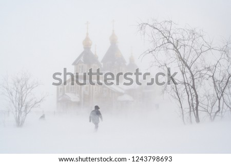 In winter, during a blizzard near the Cathedral of the Holy Trinity. People go through a snowstorm.Anadyr city, Chukotka, Russia.