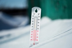 In winter or spring the thermometer lies on the snow and shows a negative temperature in cold weather.Meteorological conditions with low air and ambient temperatures.Climate change and global warming