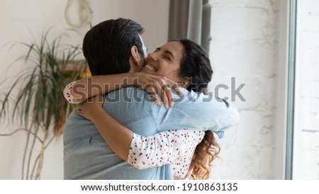 In your warm embraces. Excited wife holding beloved husband tight in arms grateful for support love care. Young couple hug reconciling after family fight or missing each other spending long time apart Stock photo ©