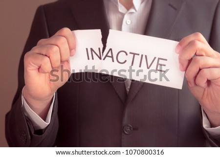 inactive is active concept. Hand holding card with text inactive, tearing off word in. Conceptual image of changing position from inactive to active.