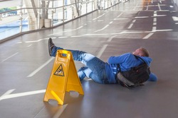 Inattentive man has fallen down on wet floor in spite of the big yellow warning sign