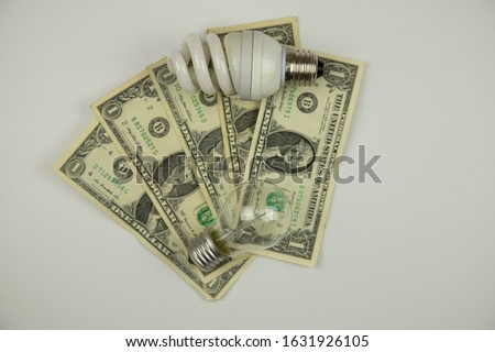 incandescent and fluorescent lamps lie on one-dollar bills