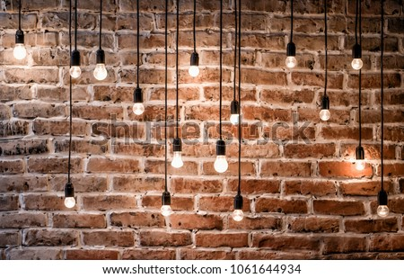 Incandescent bulbs on brick wall background in loft style