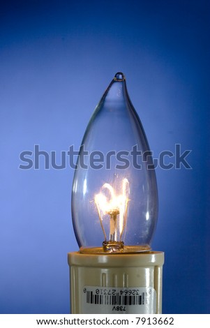 Incandescent clear light bulb lighting up blue background