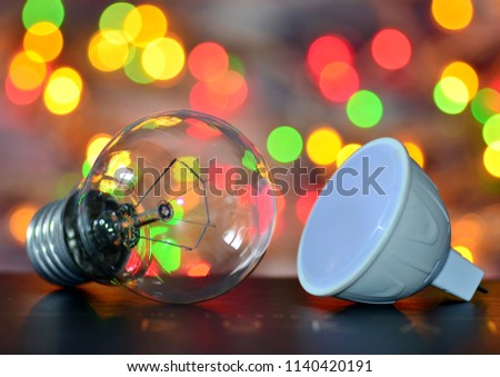 Incandescent lamp and LED lamp on a background of a colorful bokeh