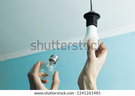 Incandescent lamp is changed to LED light by the hands of a man. Energy saving.