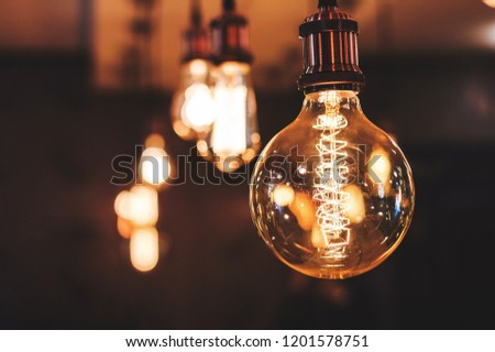 incandescent lamp with an unusual spiral. A lamp in the room with other lamps that are out of focus.