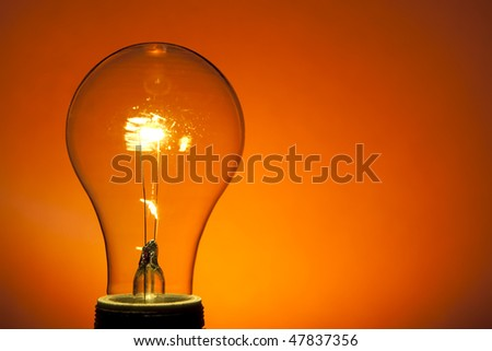 Incandescent Light Bulb on Orange. Spot lit background. Studio lit.