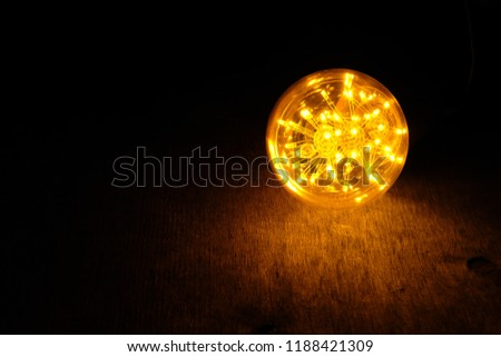 Incandescent light bulb on wooden board.