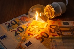 Incandescent light bulb turned on, with banknotes and coins beside it, on wooden surface. Electricity costs.