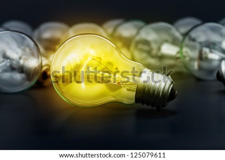 Incandescent light bulbs on dark surface with the center one lighting