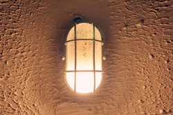 incandescent warm light burning in an old lamp hanging on a concrete wall in a dark gloomy corridor